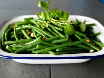 Green beans and watercress served in a white enamel dish