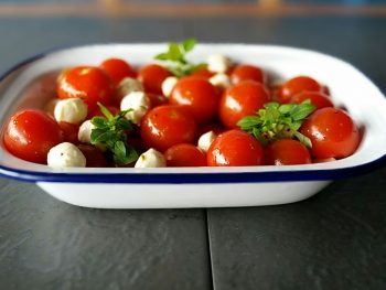 Baby tomatoes served with mozzarella balls and basil