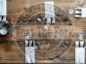 table layout for five people on a wooden table with flowers and What The Fork's logo